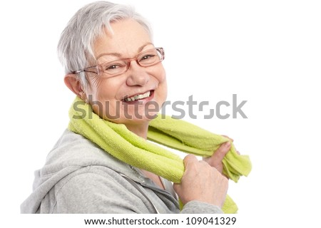 Energetic old woman smiling after workout, holding towel around neck.