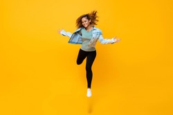 Energetic portrait of smiling happy young African American woman jumping isolated on yellow background