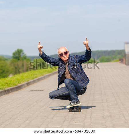 energetic senior man enjoying riding a skateboard. The concept of life satisfaction. Portrait of a positive gray-haired man with a skateboard. winner concept.
