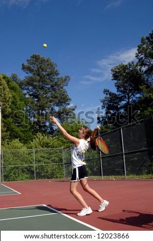 Energetic teen serves tennis ball during a high school tennis match.  Uniform is black skirt and white tee shirt.