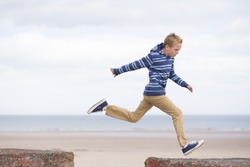 Energetic teenage boy jumping from one rock to another with the beach in the background.