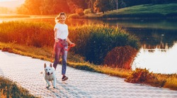 Energic caucasian girl dressed in blue jeans is running in the park with her white dog during a summer evening