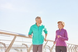 Energize your life. Active mature family couple in sportswear smiling at each other while running together on a sunny morning. Joyful senior couple working out outdoors