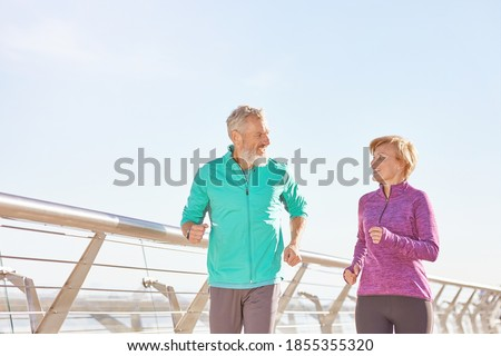 Energize your life. Active mature family couple in sportswear smiling at each other while running together on a sunny morning. Joyful senior couple working out outdoors Foto stock ©