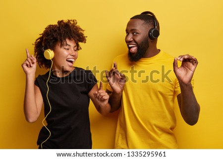 Energized black male and female dance happily, smile broadly, turn at camera, wears headphones, pick right song for good mood, dressed casually, isolated over yellow background. Music concept