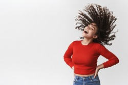 Energized lively happy good-looking joyful girl curly dark hairstyle waving shaking head curls flying air laughing cheerful dancing having fun showing-off perfect haircut standing white background