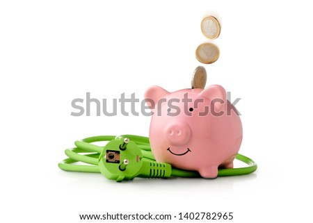 Energy costs - saving energy is good for climate protection and saves money. Euro coins fall into the piggy bank. Next to the piggy bank is a green power cord with plug #1402782965