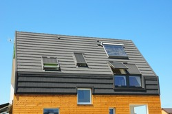 Energy Efficiency New Passive House Building Concept. Closeup of Solar Water Panel Heating, Dormers, Solar Panels, Skylights, Ventilation and Air Conditioning Systems Installed