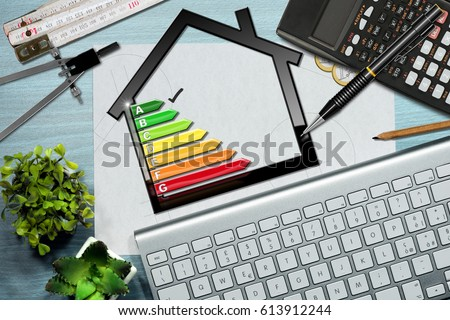 Energy efficiency rating graph on a desk with a house model, calculator, folding ruler, drawing compass, pencils and a computer keyboard