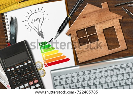 Energy efficiency rating graph on a desk with a wooden house model, calculator, folding ruler, light bulb and a computer keyboard Foto stock ©