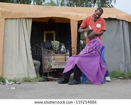 Energy efficient African small business barber with inverter and car batteries in trolley
