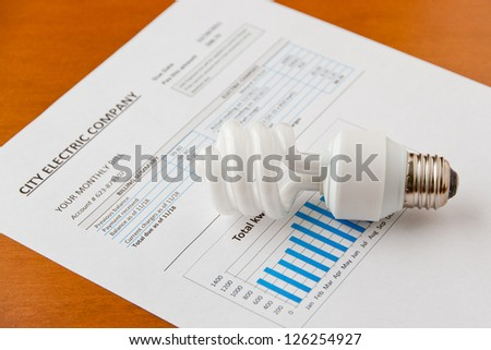 Energy efficient CFL bulb on electric bill. Energy efficient house concept.  selective focus