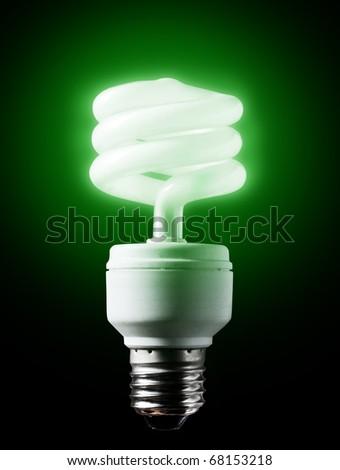 Energy-efficient  green bulb shining black background.