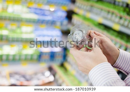Energy efficient lighting choice: closeup on hands holding or selecting LED diode light bulb lamp in DIY department store