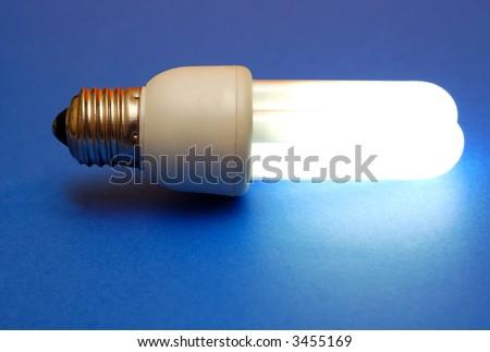 Energy efficient lit light bulb on blue background.