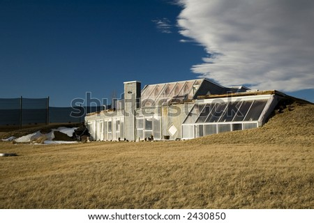 Energy efficient solar heated home made from cement and partially covered in the earth. - stock photo