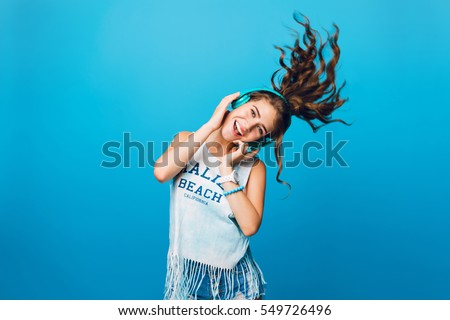 Energy girl with blue headphones  listening to music on blue background in studio. She wears white T-shirt, shorts. Long curly hair in tail is flying overhead from jump.