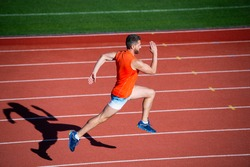 Energy inside. runner on racetrack. challenge and competition. marathon speed. sport athlete run fast to win. successful fitness sprinter. male coach on stadium running track. endurance and stamina