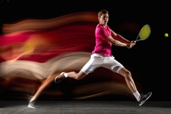 Energy, power. Young man, male tennis player in white pink sportwear playing tennis in mixed neon light on dark background. Concept of motion, force, speed, healthy lifestyle, professional sport.