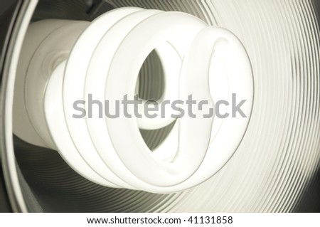 Energy saving compact fluorescent bulb glowing inside a round metal dish