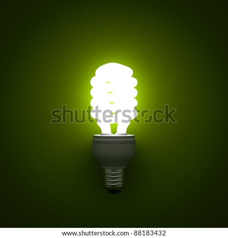 Energy saving compact fluorescent light bulb glowing on green background