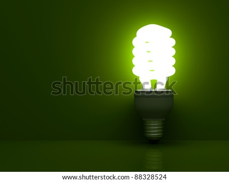 Energy saving compact fluorescent light bulb glowing on green background with reflection