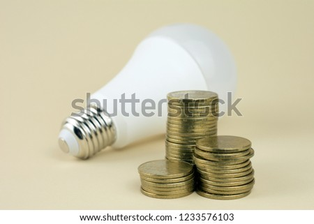 energy saving lamp and coins. how to save electricity concept #1233576103