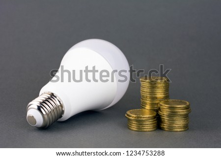 energy saving lamp and coins on gray background. using less energy reduces energy costs concept