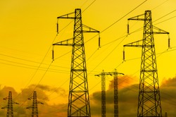 Energy  Transmission towers or electricity pylons with golden sky and clouds