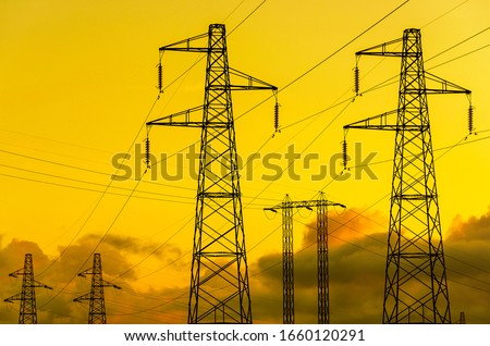 Energy  Transmission towers or electricity pylons with golden sky and clouds Photo stock ©