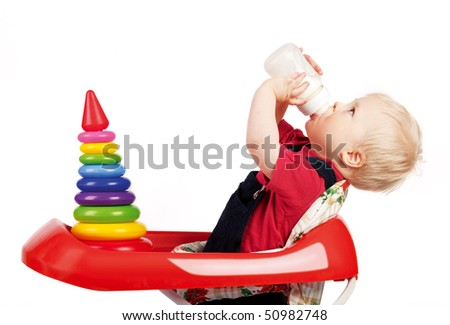 Enfant drinking milk from baby bottle on white background
