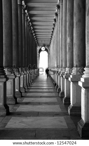 Enfilade of columns and lonely human silhouette. Black and white