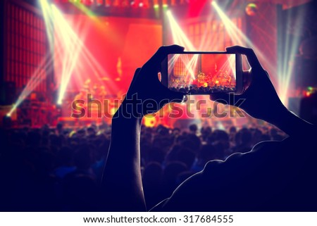 engage your audience Crowd with the power of social network by Smart phones, silhouette of a man use mobile phone camera enjoying the concert. #317684555