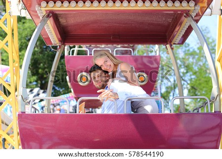 Engaged couple of elegantl people hugging, posing for photo, ride on ferris wheel, smiling, laughing and sit in booth ferris wheel on background of sky and trees at an amusement park outdoors. Girl #578544190