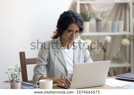 Engaged in work. Happy millennial businesswoman negotiating with client supplier by email messenger. Young lady florist designer using laptop at office studio promoting selling product service online