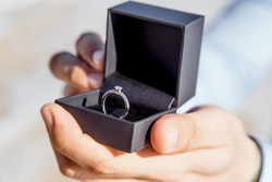 Engagement ring for romantic outdoor elopement marriage proposal when man proposing and holding up an engagement ring in box