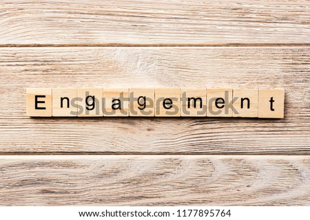 engagement word written on wood block. engagement text on table, concept.