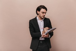 Engaging young businessman with brunette hair, trendy glasses, white shirt and classic suit, making notes and looking down. Man posing isolated over beige background