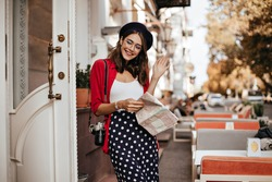 Engaging young lady with brunette hair and beret in French style outfit, camera on shoulder, holding map and smiling at cafe terrace against background of autumn city