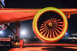 Engine and chassis of passenger jet plane in the night. Front view. Aircraft air intake and fan blades close up.