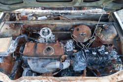 Engine bay of a burned out car in a country lane.