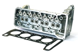 Engine cylinder head and cylinder head gasket close-up on white background. Concept of spare parts for passenger cars.