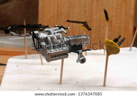 Engine, Gearbox, suspension elements, timing belt. Large-scale assembly of models. Dry painted plastic parts of cars. Hold on to the toothpicks stuck in the foam.
