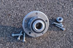 Engine gears. Auto motor mechanic spare or automotive piece on dark road asphalt background. Tarmac dark grey grainy road. Black bituminous textured waterproofing