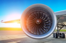 Engine of the modern aircraft close up and the sunset in the sky