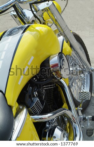 Engine, tank and front wheel of large, classic, yellow motorcycle