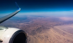 Engine Wing airplane sky concept. View of engine plane from window airplane see wing and sky and desert. It flying over above on desert beauty.