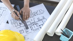 Engineer and Architect concept, Man uses a ruler to measure the floor plan on the blueprint, Building architecture design work, Construction design project under environmental conservation conditions.