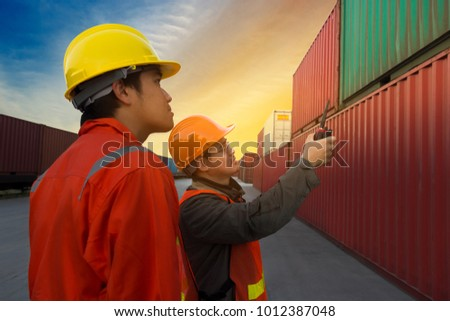 Engineer and Foreman check security and safety for the best shipping of cargo in the container yard port.