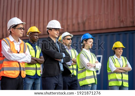 Engineer and Foreman control loading container at commercial dock cargo freight shipping, Teamwork inspecting container shipment warehouse import export global business, Cooperation team worker day. Photo stock ©